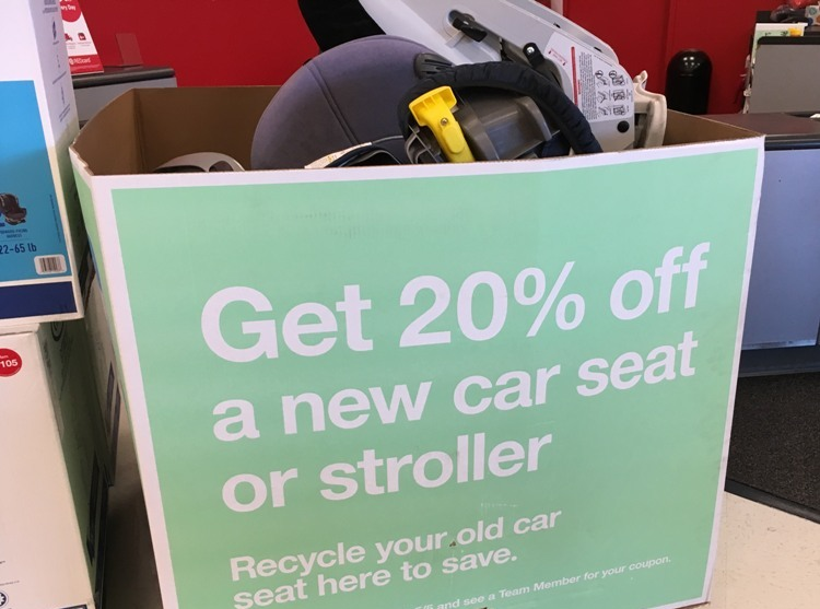 "A box advertising the target car seat trade-in program says ""Get 20% off a new car seat or stroller - Recycle your old car seat here to save."""